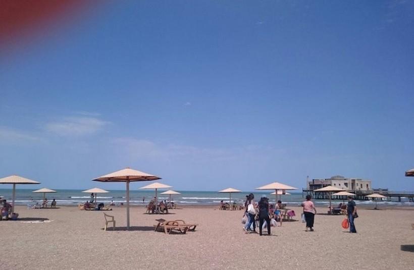 Туристы покидают пляж в Мардакянах, близится июльский полдень.