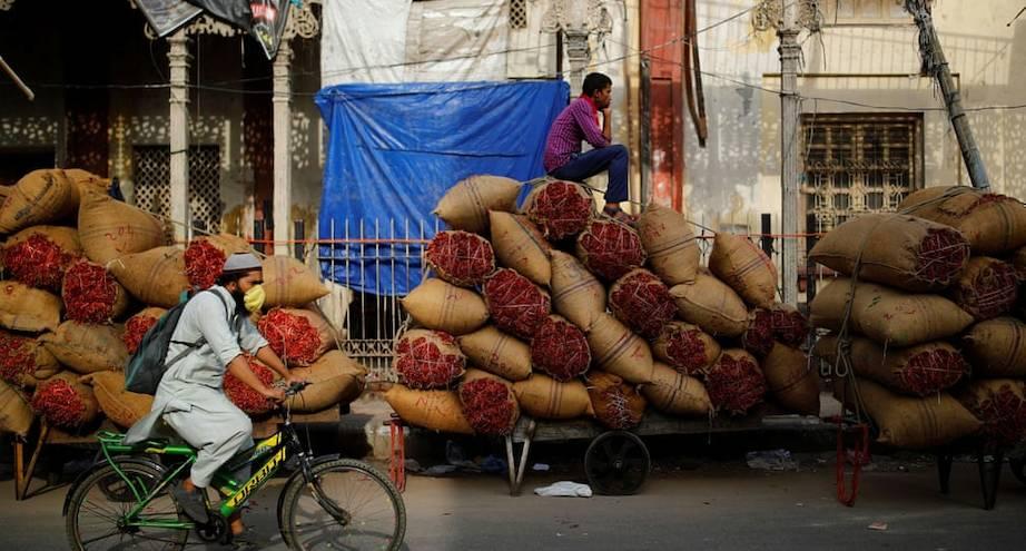 Фото дня: житель Индии на мешках со специями