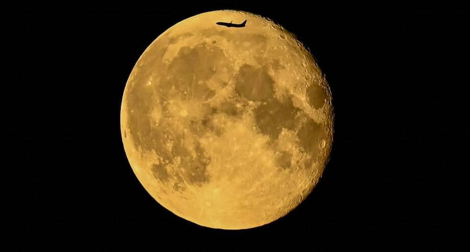 Фото дня: самолет на фоне луны